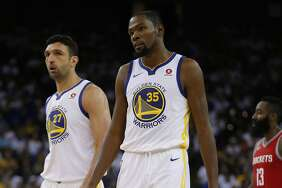 Golden State Warriors forward Kevin Durant (35) and center Zaza Pachulia (27) react as Houston Rockets guard James Harden (13) is in the background during the third quarter of an NBA game between the Golden State Warriors and the Houston Rockets at Oracle Arena on Tuesday, Oct. 17, 2017.