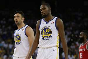 Golden State Warriors forward Kevin Durant (35) and center Zaza Pachulia (27) react as Houston Rockets guard James Harden (13) is in the background during the third quarter of an NBA game between the Golden State Warriors and the Houston Rockets at Oracle Arena on Tuesday, Oct. 17, 2017, in Oakland, Calif. The Warriors lost the basketball game 122-121.