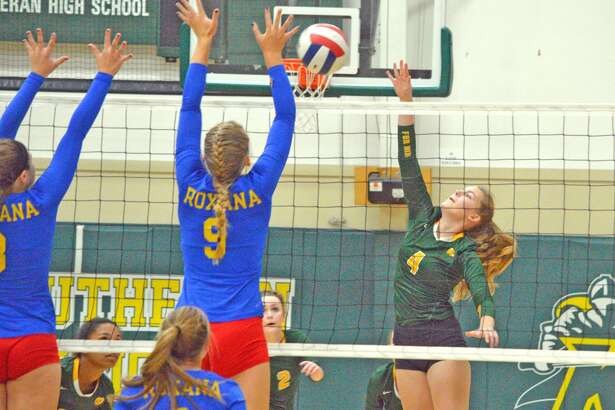 Metro-East Lutheran sophomore Alaina Bozarth, right, goes up for a kill during the first game of Wednesday's home match against Roxana.