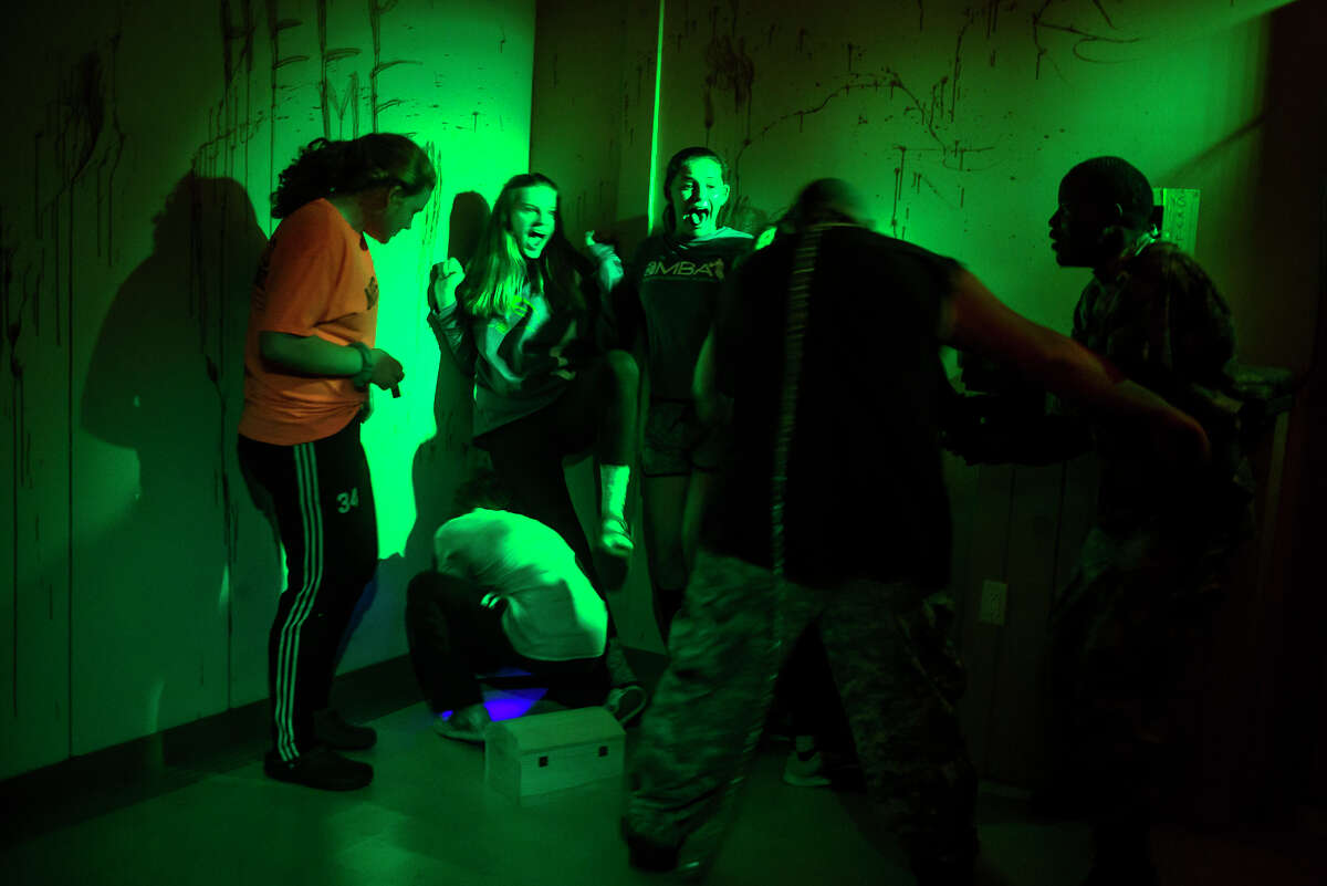 Jade Dawson, 13, center left, and Sydney Miller, 13, center right, scream as they walk through the Zombie Escape Fear Fest haunted attraction on Friday, Oct. 13 in Midland. (Katy Kildee/kkildee@mdn.net)
