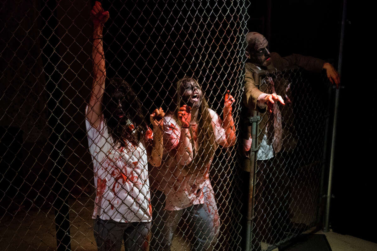 Actors dressed as zombies shake a chain link fence to scare visitors on the other side as they walk through the Zombie Escape Fear Fest haunted attraction on Friday, Oct. 13 in Midland. (Katy Kildee/kkildee@mdn.net)