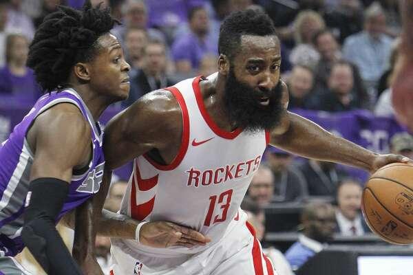 Houston Rockets guard James Harden (13) drives around Sacramento Kings defender DeAaron Fox (5) during the first half of an NBA basketball game in Sacramento, Calif., Wednesday, Oct. 18, 2017. (AP Photo/Steve Yeater)