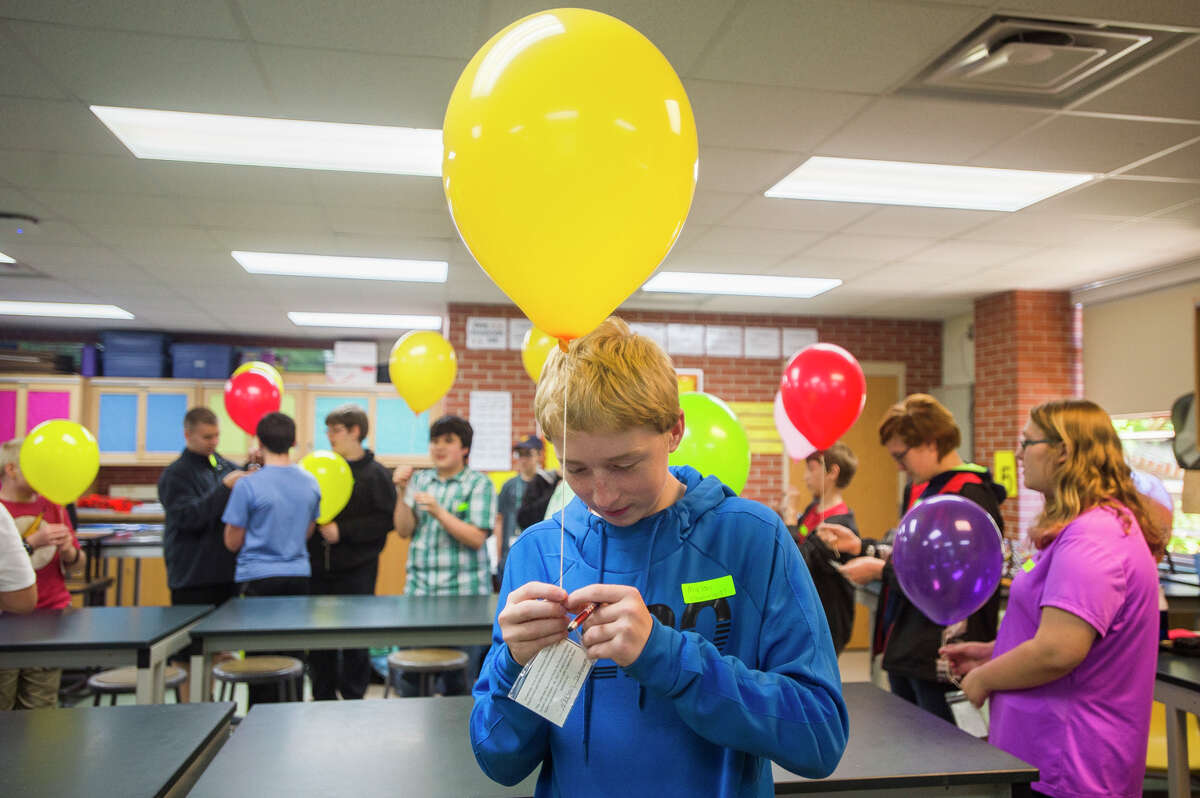 Mason Zimmerman, 13, attaches a small note to a balloon he plans to release along with dozens of other students at Northeast Middle School on Wednesday, Oct. 18, 2017. A larger weather balloon with instruments that will record data was also released. (Katy Kildee/kkildee@mdn.net)