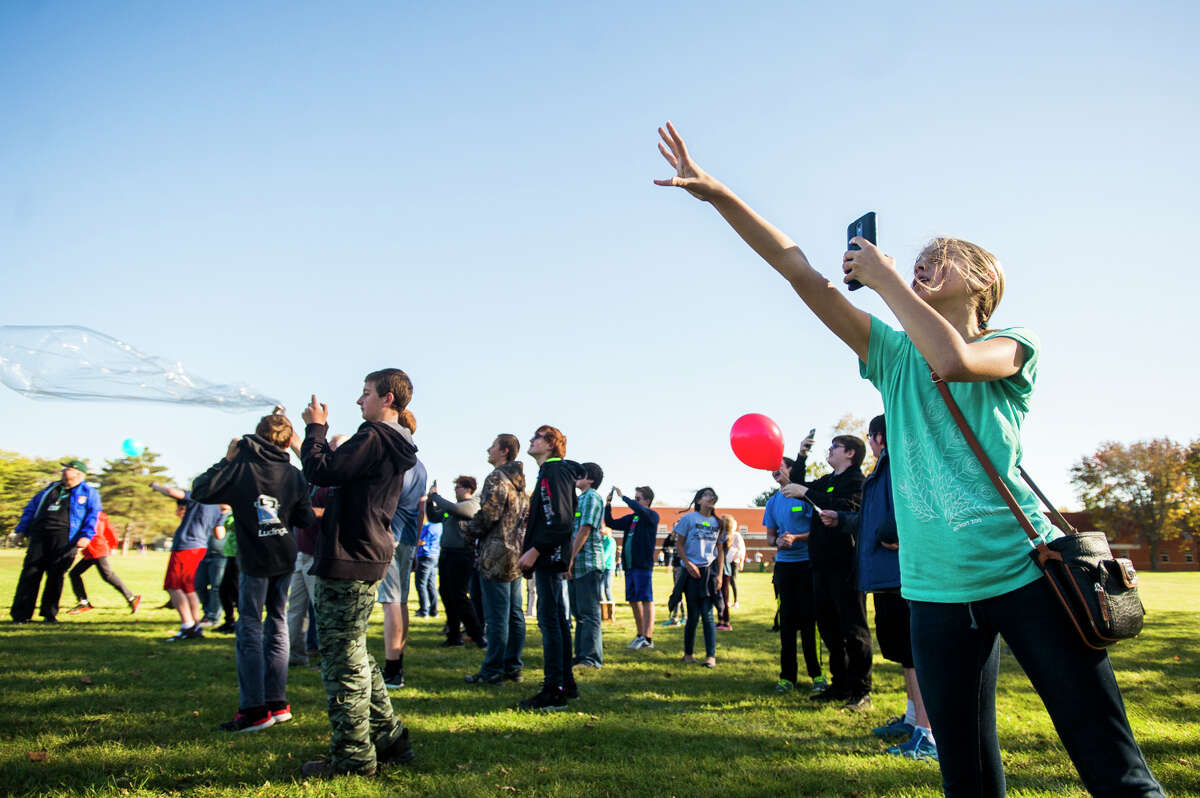 Evelyn Moor, 13, holds her hand out after releasing her balloons into the air along with dozens of her Northeast Middle School classmates on Wednesday, Oct. 18, 2017. A larger weather balloon with instruments that will record data was also released. (Katy Kildee/kkildee@mdn.net)