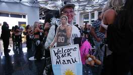 Spurs fan Mary Lou Rodriguez carries her homemade signs to welcome back the team - especially Manu Ginobili - before Spurs against Minnesota Timberwolves season opener at the AT&T Center on Wednesday, Oct. 18, 2017. (Kin Man Hui/San Antonio Express-News)