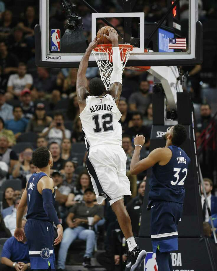Spurs' LaMarcus Aldridge (12) dunks against Minnesota Timberwolves' Karl-Anthony Towns (32) and Tyus Jones (01) in the fourth at the AT&T Center on Wednesday, Oct. 18, 2017. Spurs defeated the T'Wolves, 107-99. (Kin Man Hui/San Antonio Express-News) Photo: Kin Man Hui, Staff / San Antonio Express-News / ©2017 San Antonio Express-News