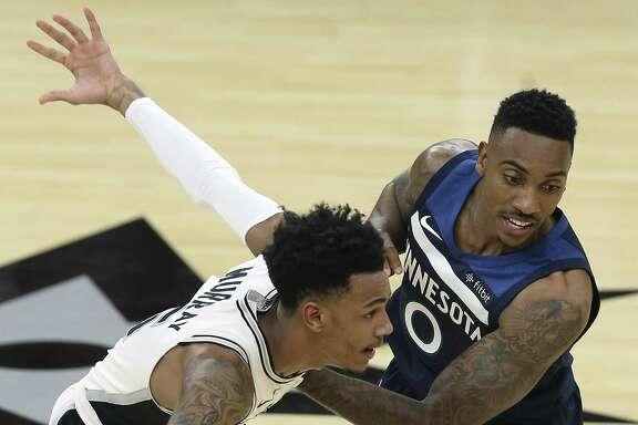 Dejounte Murray gets by Jeff Teague as the Spurs play Minnesota in the season opener at the AT&T Center on October 18, 2017.