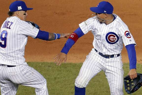 Chicago Cubs second baseman Javier Baez (9) and left fielder Jon Jay celebrate the team's 3-2 win over the Los Angeles Dodgers in Game 4 of baseball's National League Championship Series, Wednesday, Oct. 18, 2017, at Wrigley Field in Chicago. (Steve Lundy/Daily Herald via AP)
