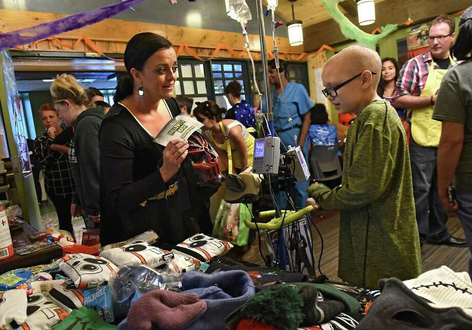 T.J. Petry, 10, of Margaretville, N.Y. picks out a Halloween costume with the help of Tara-Marie Coyne, district manager Spirit Halloween, as volunteers from local Spirit Halloween stores bring fun, festivities and Halloween to patients and families at the Bernard & Millie Duker Children's Hospital at Albany Medical Center on Wednesday, Oct 18, 2017 in Albany, N.Y. T.J was in the hospital to get chemo treatment. (Lori Van Buren / Times Union) Photo: Lori Van Buren / 20041879A