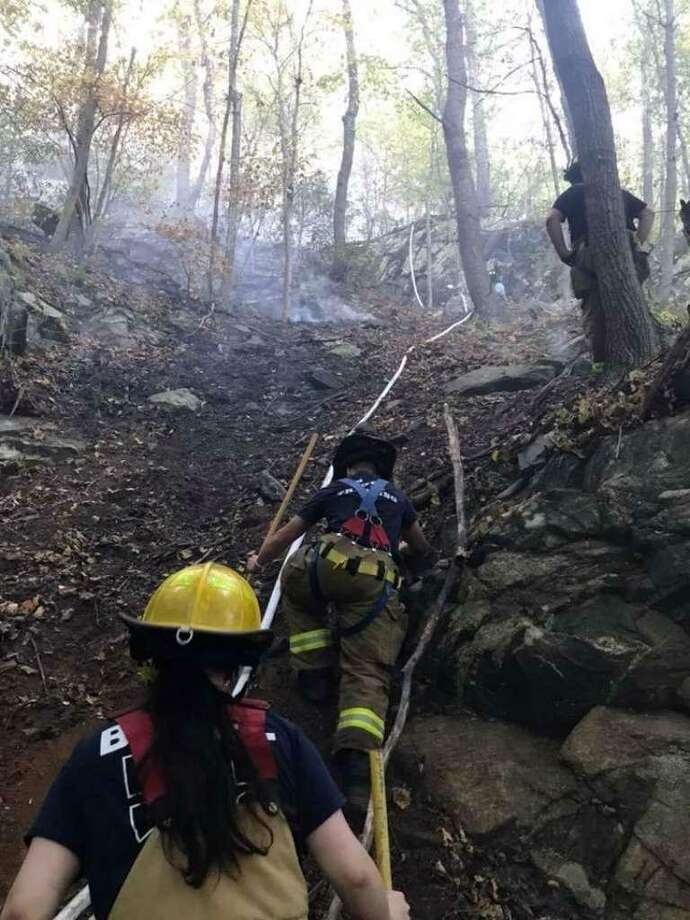 Members of the Bethel Volunteer Fire Department climb a steep slop at Terra Haute Wednesday in an effort to reach a brush fire that erupted in the area. From bottom to top are Firefighters Erin Murphy, Mitch Palumberi and Dawson Brown. Photo: / Contributed