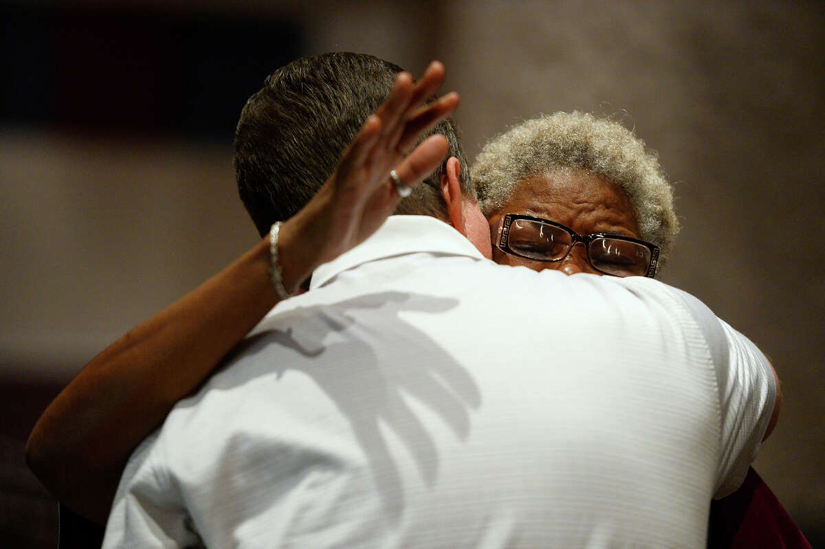 Chris Bottoms, a pastor at Friendship Baptist Church and a high school teacher, hugs a woman during a vigil at Silsbee High School for Ashley Pickering and her five children, who were killed in a house fire on Wednesday. Photo taken Wednesday 10/18/17 Ryan Pelham/The Enterprise
