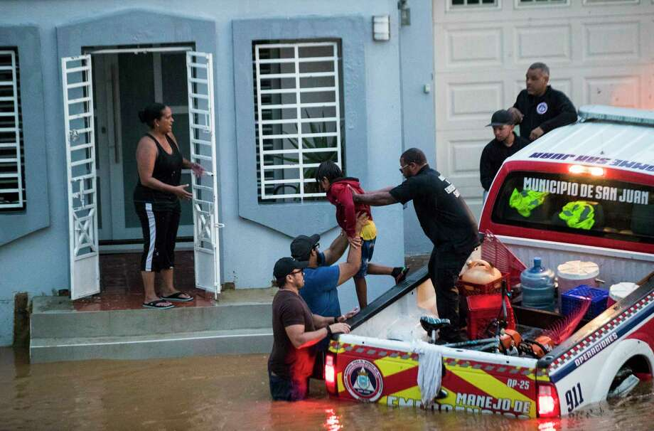 Members emergency management of the city of San Juan hand a child who was up to his neck in flood waters during a torrential rain, 18 days after Hurricane Maria, Sunday, Oct. 8, 2017, in San Juan. Almost a month after the hurricane, the island of Puerto Rico is still struggling to clear up the debris from the hurricane to avoid floods. Photo: Marie D. De Jesus, Houston Chronicle / © 2017 Houston Chronicle