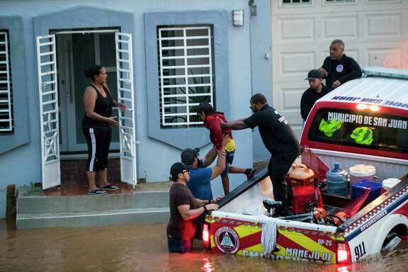 Members emergency management of the city of San Juan hand a child who was up to his neck in flood waters during a torrential rain, 18 days after Hurricane Maria, Sunday, Oct. 8, 2017, in San Juan. Almost a month after the hurricane, the island of Puerto Rico is still struggling to clear up the debris from the hurricane to avoid floods.