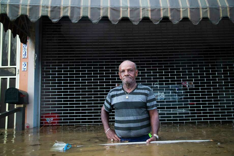Maximiliano Encarnacion a resident of San Juan, Puerto Rico, holds a broom he used to push away debris carried by the flood waters caused by a torrential rains, Sunday, Oct. 8, 2017, in San Juan, 18 days after Hurricane Maria touchdown in Puerto Rico. Almost a month after the hurricane, the island of Puerto Rico is still struggling to clear up the debris from the hurricane to avoid floods. Photo: Marie D. De Jesus, Houston Chronicle / © 2017 Houston Chronicle