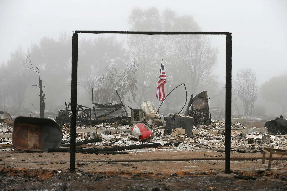 An American flag flies at a home destroyed by last week's destructive Tubbs Fire on Walnut Grove Street in the Coffey Park neighborhood of Santa Rosa, Calif. on Wednesday Oct. 18, 2017.