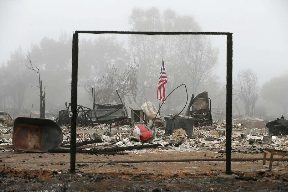 An American flag flies at a home destroyed by last week's destructive Tubbs Fire on Walnut Grove Street in the Coffey Park neighborhood of Santa Rosa, Calif. on Wednesday Oct. 18, 2017. Photo: Paul Chinn / The Chronicle