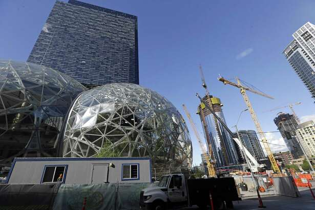 In this Wednesday, Oct. 11, 2017, photo, large spheres take shape in front of an existing Amazon building, behind, as new construction continues across the street in Seattle. (AP Photo/Elaine Thompson)