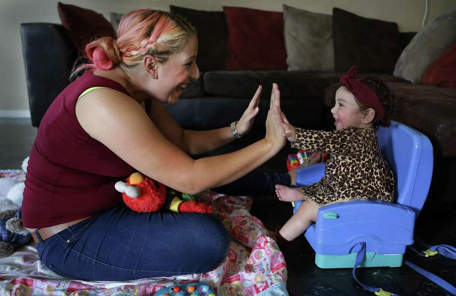 Victoria Ortiz, 30, and her 10-month-old daughter Gracie Guajardo play at her sister's house. Ortiz has overcome opioid addiction, including heroin, and now is a mainstay at a support group for mothers who gave birth to addicted babies. Photo: Bob Owen, Staff / San Antonio Express-News / ©2017 San Antonio Express-News