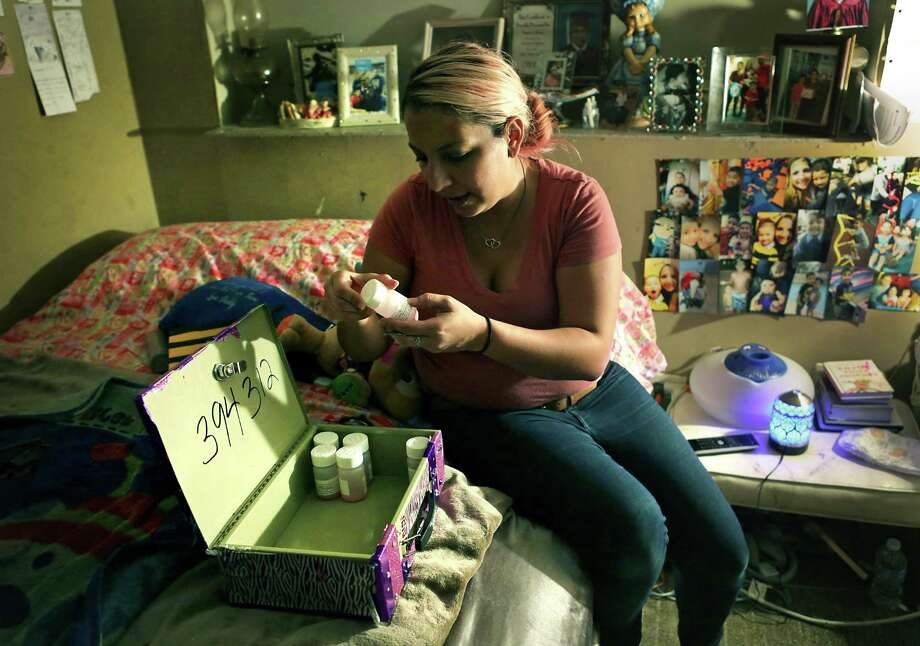 Victoria Ortiz, 30, inspects her doses of methadone kept in a personalized locked metal case in her room at her parent's house in October. Methadone clients who have proved adherence to the program can take their medication home, as opposed to coming to a clinic each day. Photo: Bob Owen, Staff / San Antonio Express-News / ©2017 San Antonio Express-News