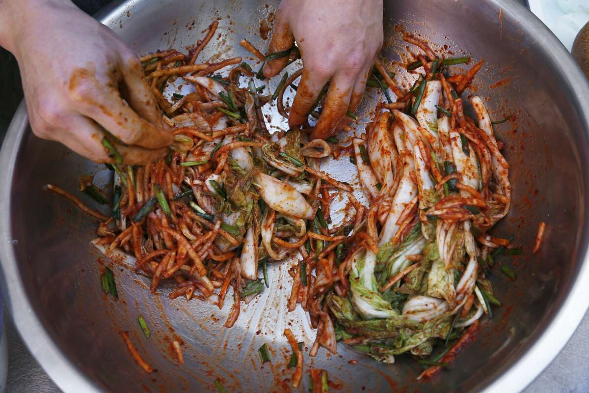 Chef Steve Joo hand mixes the ingredients used to create their Kim Chi. Chefs Julya Shin and Steve Joo are the owners of a Korean ssam pop-up called Nokni, as seen on Mon. Sept.. 25, 2017, in Oakland, Ca.