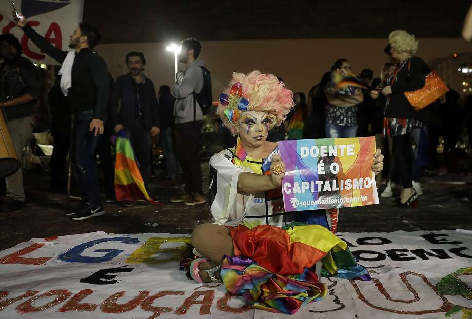 "In this Sept. 29, 2017 photo, an activist holds a sign that reads in Portuguese ""Sick is capitalism"" after a judge's decision to approve gay conversion therapy in Sao Paulo, Brazil. The judge waved aside objections from the nation's top psychologists that homosexuality can be addressed with so-called conversion therapy treated as an illness, though that was knocked down by higher courts. (AP Photo/Andre Penner) Photo: Andre Penner, Associated Press"