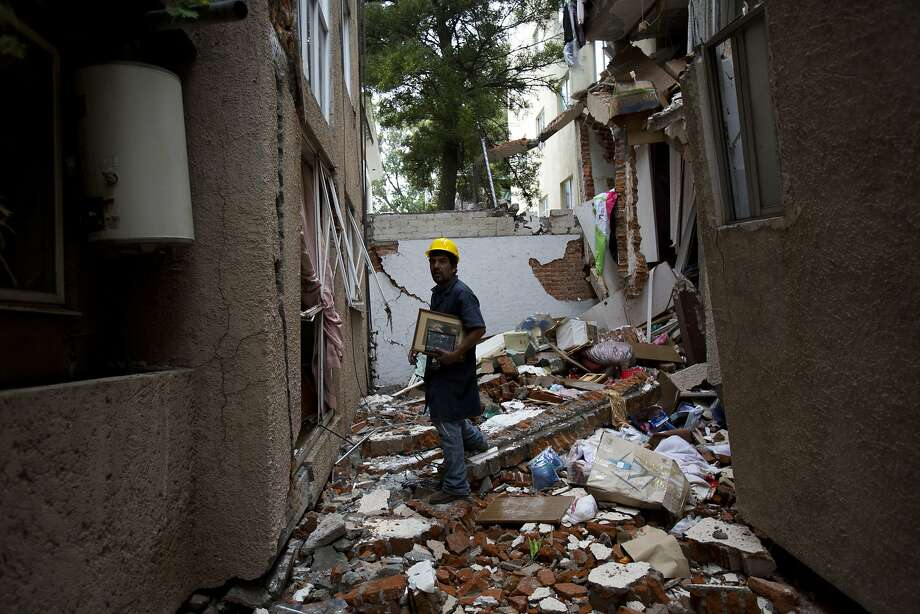 Rodrigo Diaz Mejia, 38, carries recovered family photos as he walks between two apartment buildings at Tokio 517  that collapsed in the Sept. 19 earthquake, in the Portales Norte neighborhood of Mexico City, Wednesday, Oct. 18, 2017. Diaz, a mechanic who lives on the same block, ran to help rescue people trapped atop the buildings roofs on the day of the quake and has since been making risky forays into the ruptured apartments to retrieve family photos, documents, and prized possessions for the displaced residents. (AP Photo/Rebecca Blackwell) Photo: Rebecca Blackwell, Associated Press
