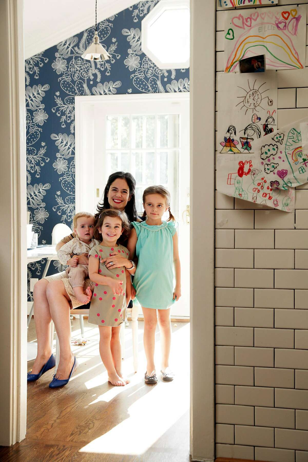 Florie Hutchinson with her daughters (R-L), Eloise, 6, Anais, 4, and Beatrice, 10 mos, in her Palo Alto, Calif., home on Monday, October 16, 2017. Hutchinson is trying to convince the Unicode Consortium that they need to include a flat shoe emoji to give women an option and prevent the over-sexualization of women.