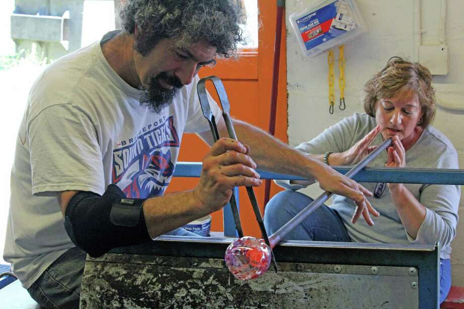 Dylan Cotton helps Pat Dellaripa create a piece of blown glass at his studio, Hot Spot, in Fairfield on Wednesday. Photo: Genevieve Reilly / Hearst Connecticut Media / Fairfield Citizen