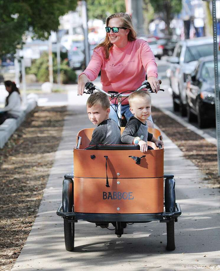 Emily Hasen of Old Greenwich transports her son's Otis, 4, left, and Cash, 2, in her Dutch Babboe bike outside the Old Greenwich School in Old Greenwich, Conn., Friday, Sept. 29, 2017. Photo: Bob Luckey Jr. / Hearst Connecticut Media / Greenwich Time