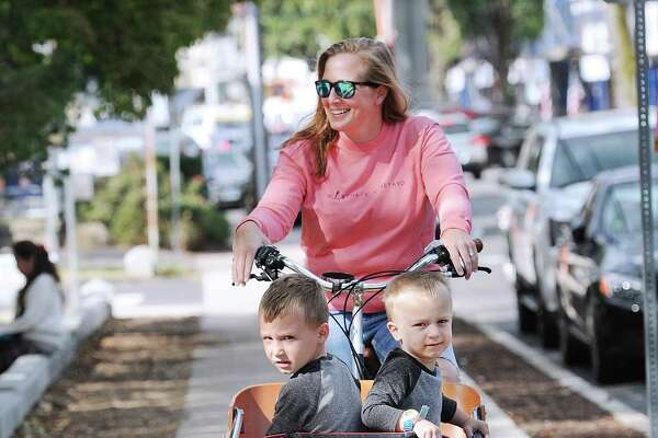 Emily Hasen of Old Greenwich transports her son's Otis, 4, left, and Cash, 2, in her Dutch Babboe bike outside the Old Greenwich School in Old Greenwich, Conn., Friday, Sept. 29, 2017.