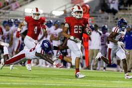 The Woodlands running back Bryeton Gilford (25) runs past the outstretch arms of Beaumont West Brook defensive back O'Brien Coleman (22) during the fourth quarter of a District 12-6A high school football game at Woodforest Bank Stadium on Thursday, Oct. 12, 2017, in Shenandoah. The Woodlands defeated Beaumont West Brook 35-21.