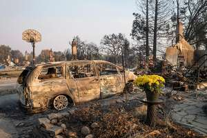 Fresh flowers stand in front of residences burned by wildfires in Santa Rosa, California, on Oct. 13, 2017. MUST CREDIT: Bloomberg photo by David Paul Morris.