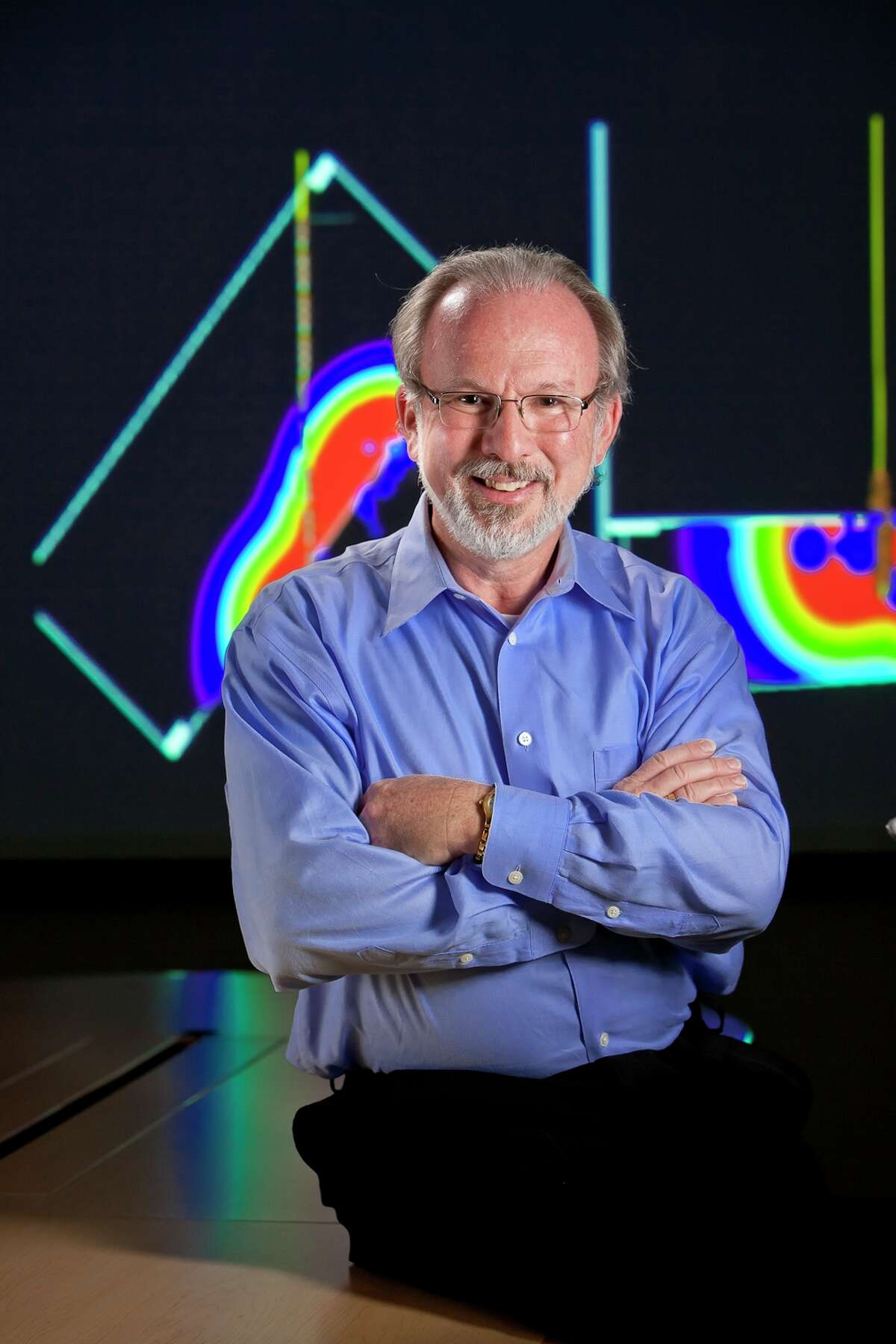 Peter Duncan, founder and CEO of Houston-based MicroSeismic, poses with a display of seismic data. The company uses monitors near the surface to capture and analyze the sounds of hydraulic fracturing far below.