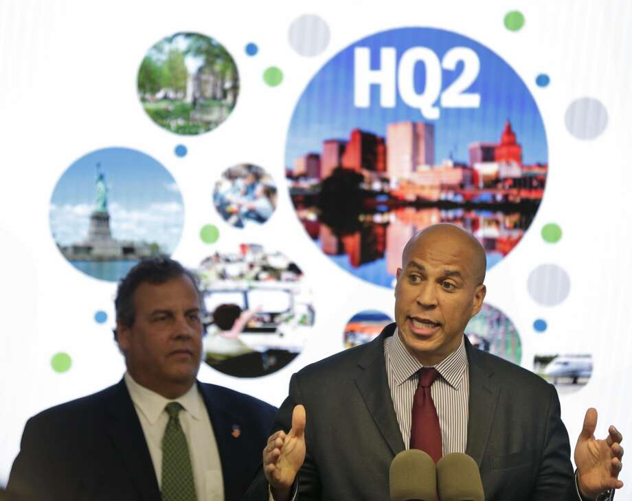 New Jersey Sen. Cory Booker, right, speaks while New Jersey Gov. Chris Christie stands behind him during an announcement in Newark, N.J. The New Jersey lawmakers announced they are submitting a bid to Amazon that Newark would be the best location for the company's planned second headquarters. (AP Photo/Seth Wenig, File) Photo: Seth Wenig/AP