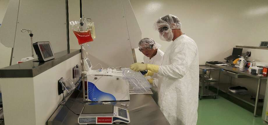 FILE - In this May 2016 file photo provided by Kite Pharma, cell therapy specialists at the company's manufacturing facility in El Segundo, Calif., prepare blood cells from a patient to be engineered in the lab to fight cancer. On Wednesday, Oct. 18, 2017, the Food and Drug Administration approved sales of the therapy Yescarta, developed by Kite Pharma, which was recently purchased by Gilead. (Kite Pharma via AP, File) Photo: Associated Press