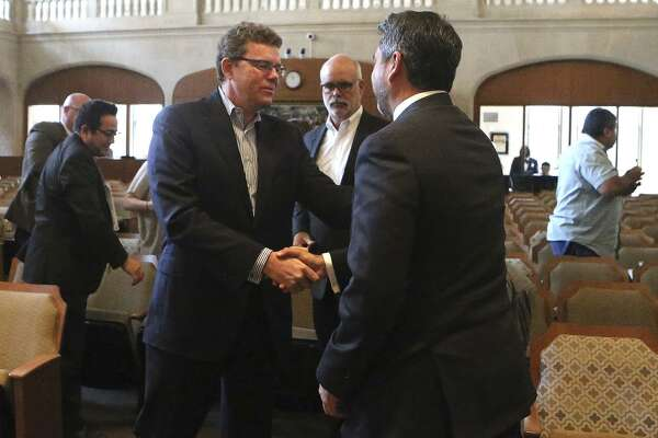 Credit Human President and CEO Stephen Hennigan (center, foreground, striped shirt) shakes hands Thursday October 19, 2017 with San Antonio city councilman Roberto Trevino (right, foreground, facing away) at city council chambers after tax abatements and other incentives were granted for Credit Human. Standing between them (background) is Bill Shown of Silver Ventures. Formerly known as San Antonio Credit Union, Credit Human will be moving to a new location at The Pearl.