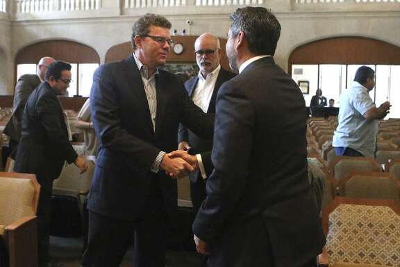 Credit Human President and CEO Stephen Hennigan shakes hands Oct. 19 with San Antonio city councilman Roberto Trevino, right, at city council chambers after tax abatements and other incentives were granted for Credit Human to relocate to the Pearl. The package raises questions.