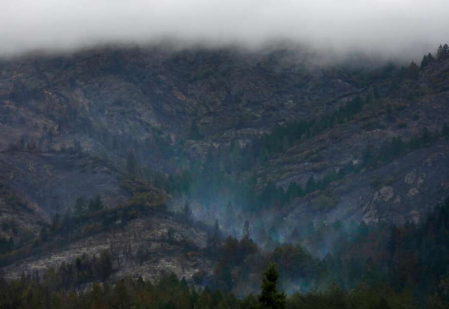 Heavy clouds containing moisture hang over a forest that continues to smoke near Sugarloaf Ridge State Park Oct. 19, 2017 in Kenwood, Calif. Photo: Leah Millis, The Chronicle