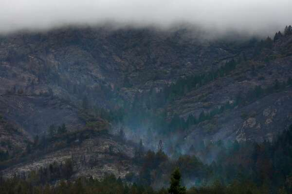 Heavy clouds containing moisture hang over a forest that continues to smoke near Sugarloaf Ridge State Park Oct. 19, 2017 in Kenwood, Calif.
