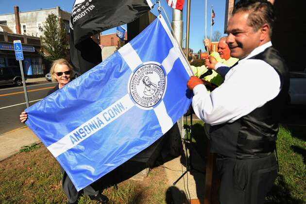 Nancy Busk Carlson, left, and Ansonia Mayor David Cassetti prepare to raise the Ansonia city flag, designed by Busk as a Ansonia High School student in 1965, in a ceremony outside City Hall in Ansonia, Conn. on Thursday, October 19, 2017. The flag has not flown in 30 years.