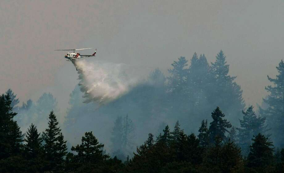 At least six helicopters join firefighters as they battle the Lockheed Fire on Aug. 14, 2009, in Bonny Doon. Photo: Michael Macor, The Chronicle