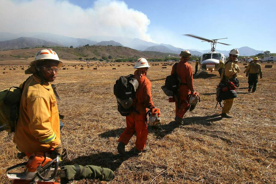 A crew prepares to board a helicopter near Ojai in 2006 to help battle the Day Fire, smoke from which rises behind it. Photo: MICHAEL A. MARIANT, AP
