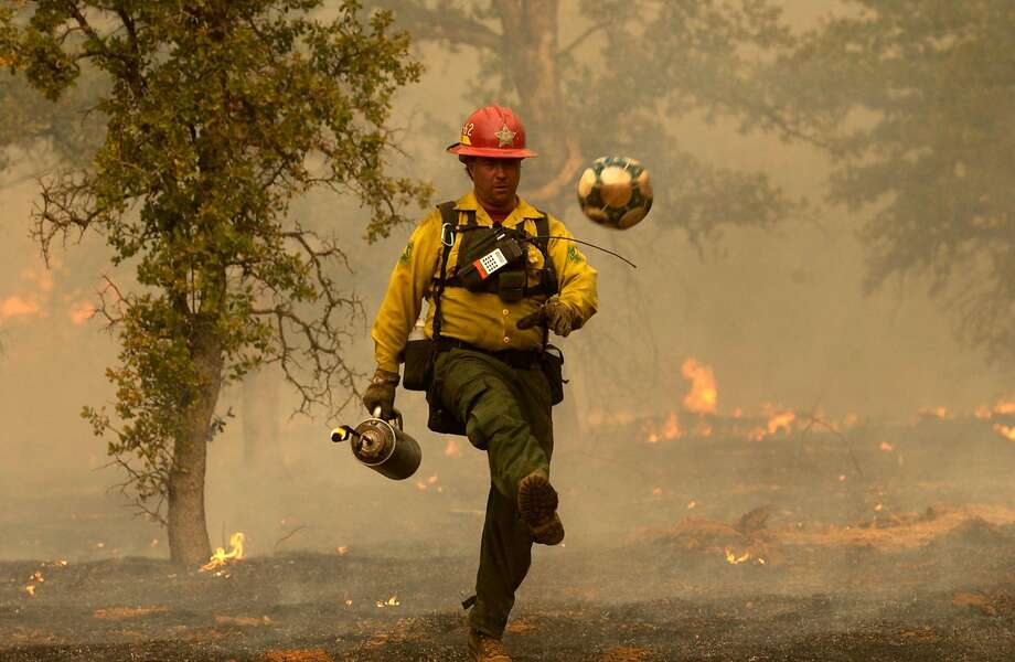 U.S. Forest Service Fire Engineer Keith Orr kicks a soccer ball out of a burned area while fighting the Bear Fire in Shasta County. Photo: LUCAS MOBLEY, AP