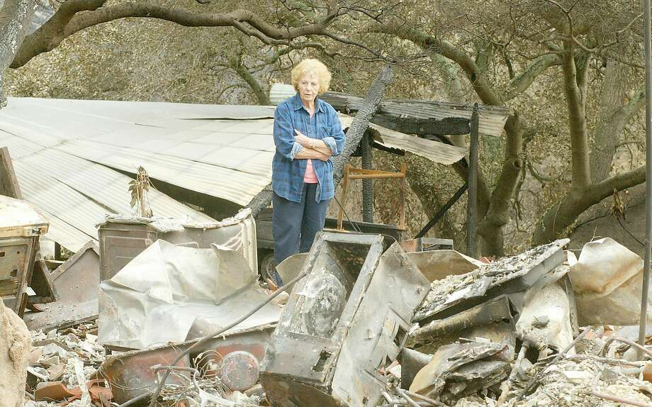 Helen McLean, 78, walks through the rubble the home her husband built along Old Barona Road in Lakeside. The family lost six homes in the Cedar Fire. Photo: MICHAEL MACOR, SFC