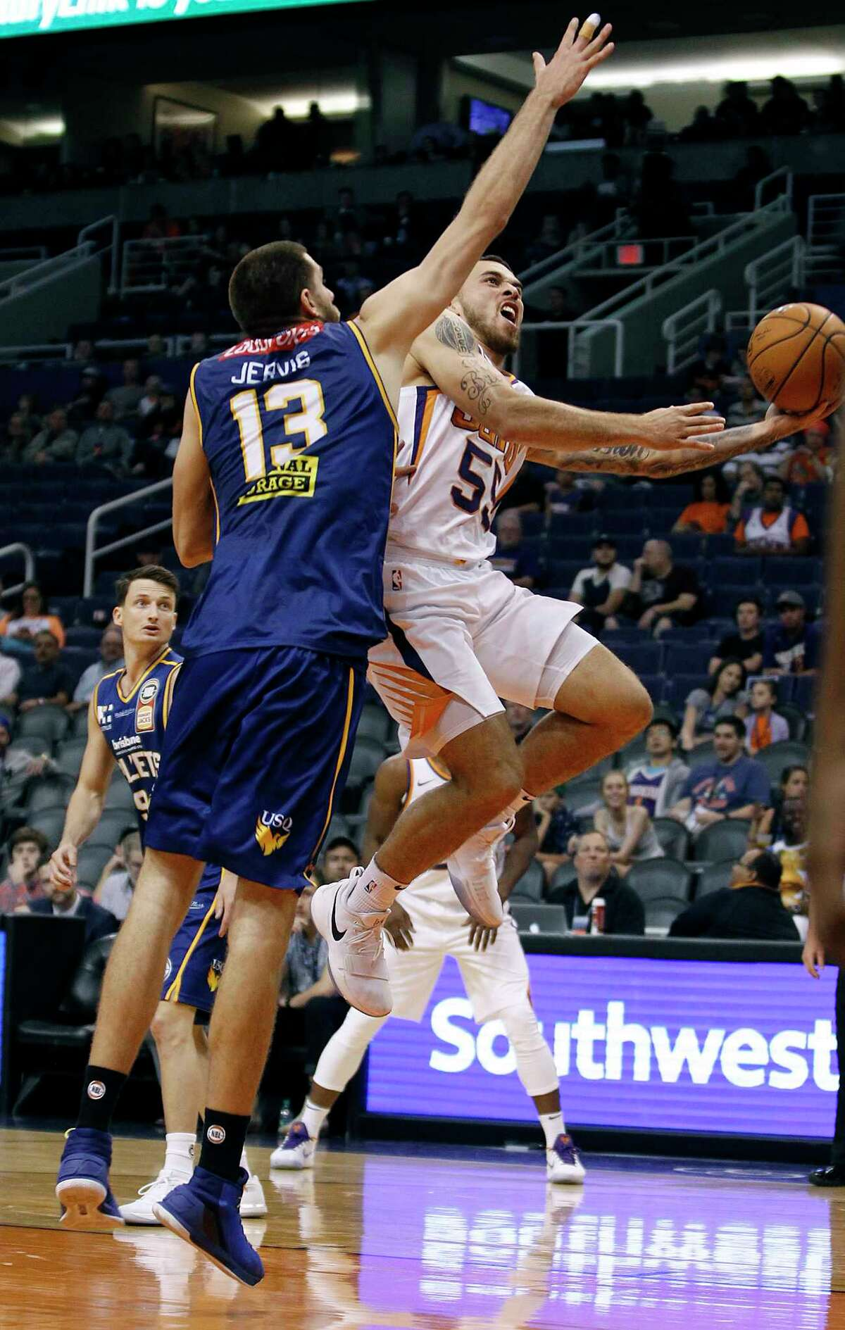 Phoenix Suns forward guard Mike James (55) drives to the basket as Brisbane Bullets forward Tom Jervis defends during the second half of an NBA basketball exhibition game Friday, Oct. 13, 2017, in Phoenix. (AP Photo/Ralph Freso)