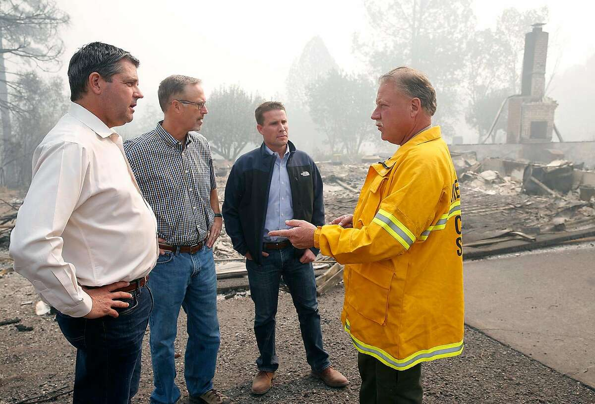 Assemblyman Jim Wood (left), Rep. Jared Huffman and state Sen. Mike McGuire are briefed on the firestorm Oct. 10 by Sheriff Tom Allman in Redwood Valley (Mendocino County).