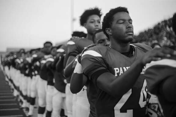 CE King High School's varsity football team lines up for the national anthem for their first game since Hurricane Harvey.