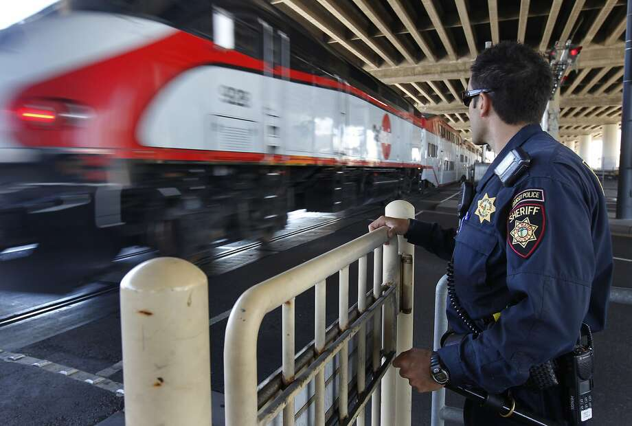 San Mateo County Sheriff's Deputy Brandon Hensel watches an inbound train cross 16th Street while approaching the Caltrain station in San Francisco, Calif. on his patrol of the commuter rail system on Wednesday, Aug. 8, 2012. Photo: Paul Chinn, The Chronicle