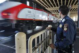 San Mateo County Sheriff's Deputy Brandon Hensel watches an inbound train cross 16th Street while approaching the Caltrain station in San Francisco, Calif. on his patrol of the commuter rail system on Wednesday, Aug. 8, 2012.