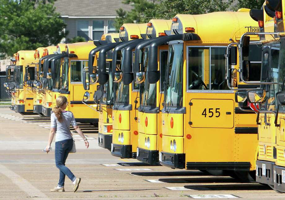 A school bus driver walks past a line of busses at a Katy Independent School District bus barn in 2014. 